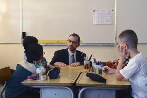 Photo d'un homme accroupi à un bureau d'enfants dans une salle de classe, visiblement échangeant avec eux